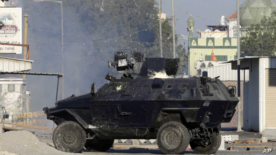 A police armored vehicle splattered with paint bombs fires tear gas toward Bahraini anti-government protesters during clashes in Sitra, Bahrain, Feb. 14, 2016.