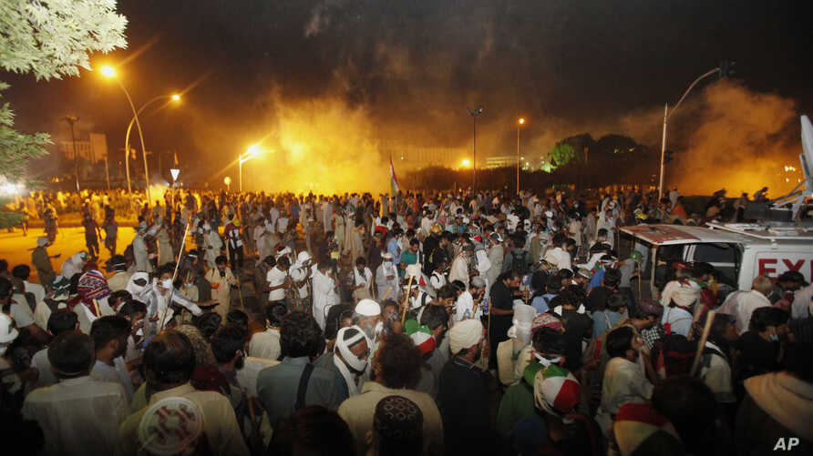 Pakistani protesters run during clashes near prime minister's home in Islamabad, Aug. 30, 3014.