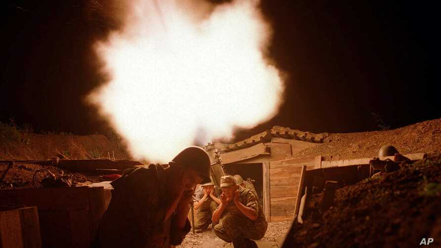 Russian soldiers protect their ears as they fire a mortar against a suspected rebel base near the Chechen village of Samashki, 30 kilometers (20 miles) west of Grozny, Chechnya, Russia, Aug. 10, 2000.