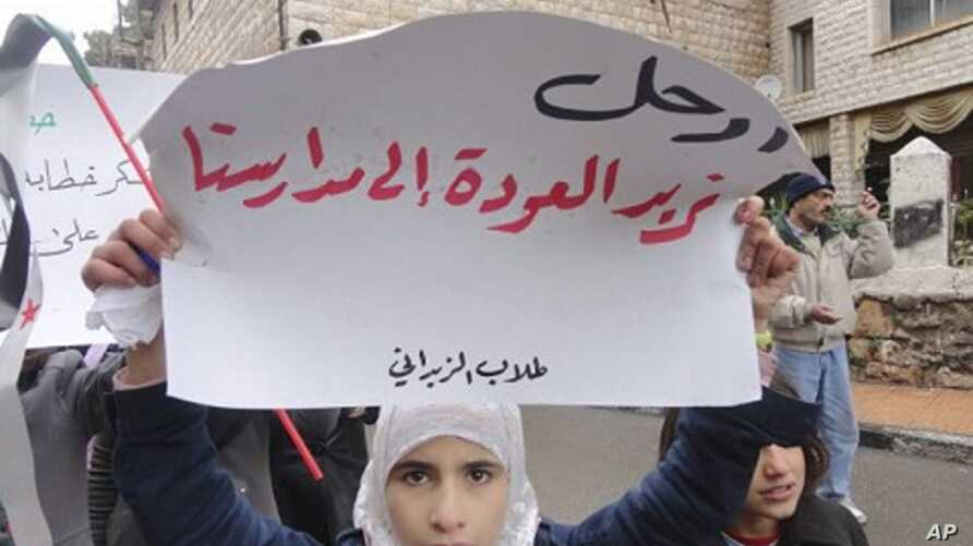 """Demonstrators protest against Syria's President Bashar al-Assad in Zabadani, near Damascus January 13, 2012. The placard reads, """"Go, we want to go back to our schools""""."""