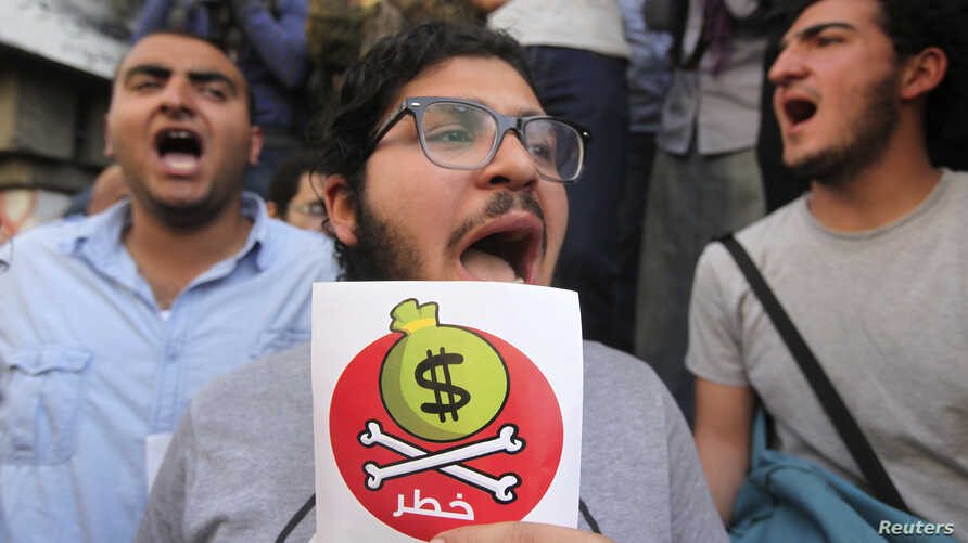 Egyptian protesters hold placards with the Arabic inscription reading 'danger' and shout slogans as they demonstrate against the International Monetary Fund (IMF) delegation visit in Cairo, April 3, 2013.