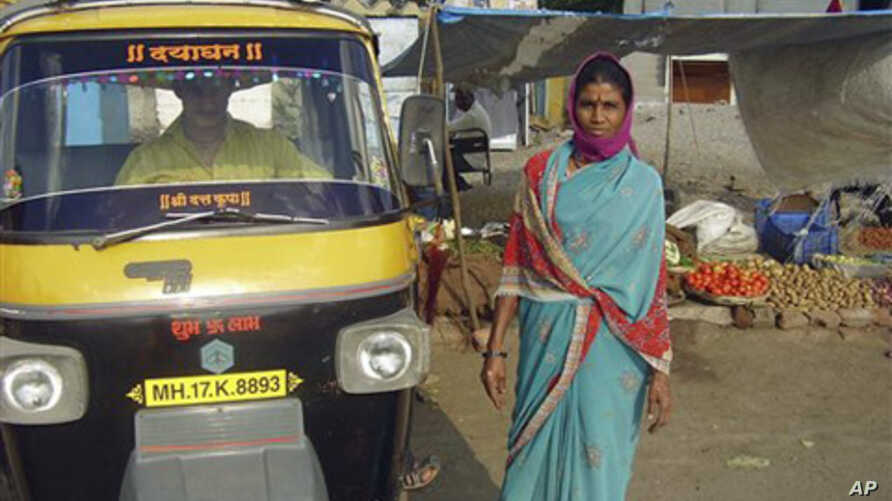 In this photo provided by Singing River International Ministries, Shobha Chothe of Ahmednagar, India, poses next to a new cab she purchased after applying for a small business loan from Singing River Internaional Ministries (FILE).