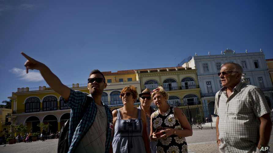 FILE - Tour guide Javier Rodriguez, left, speaks to tourists in Havana, Cuba, Jan. 18, 2018.