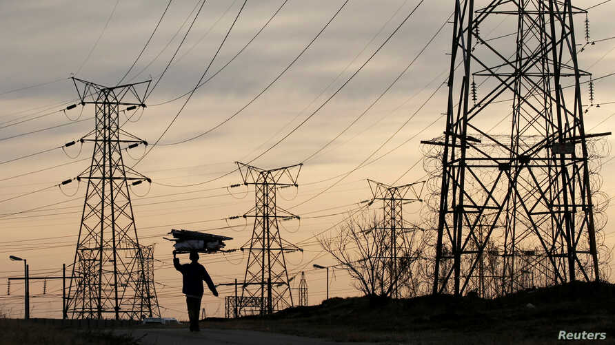 FILE - A woman carries firewood on her head as she walks below Eskom's electricity pylons in Soweto, South Africa, Aug. 8, 2016.