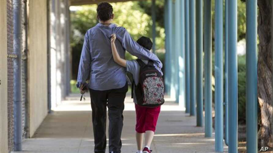 In this photo taken Monday, Aug. 13, 2012, Matthew Asner walks his son Will, 9, who is autistic, to the Nestle Avenue Elementary School in the Tarzana district of Los Angeles. Public school districts are seeing higher proportions of children with spe