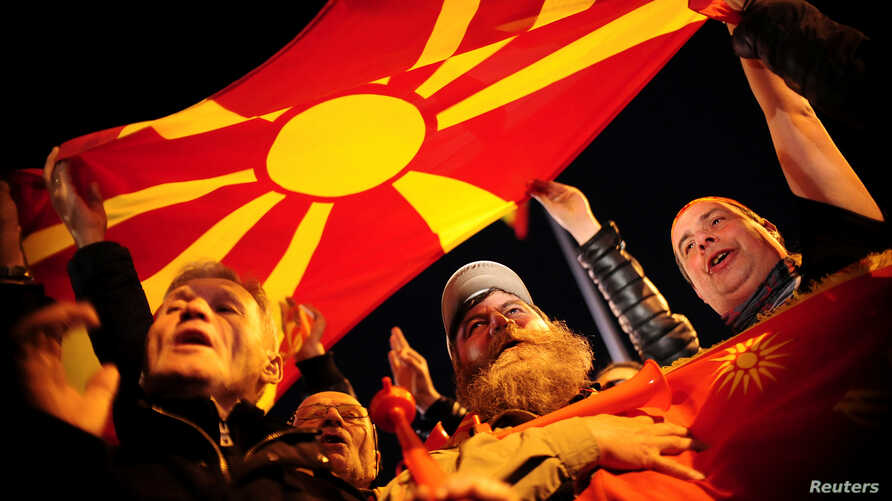 Protesters shout slogans while holding a Macedonian flag during demonstrations against an agreement that would ensure the wider use of the Albanian language in the ethnically divided state, in Skopje, Macedonia, Feb. 28, 2017.