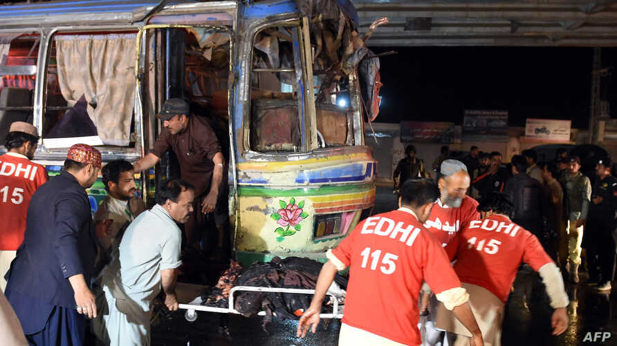 Pakistani volunteers and local residents move the body of a blast victim from a bus after a bomb explosion in Quetta, Pakistan, on Oct. 19, 2015.