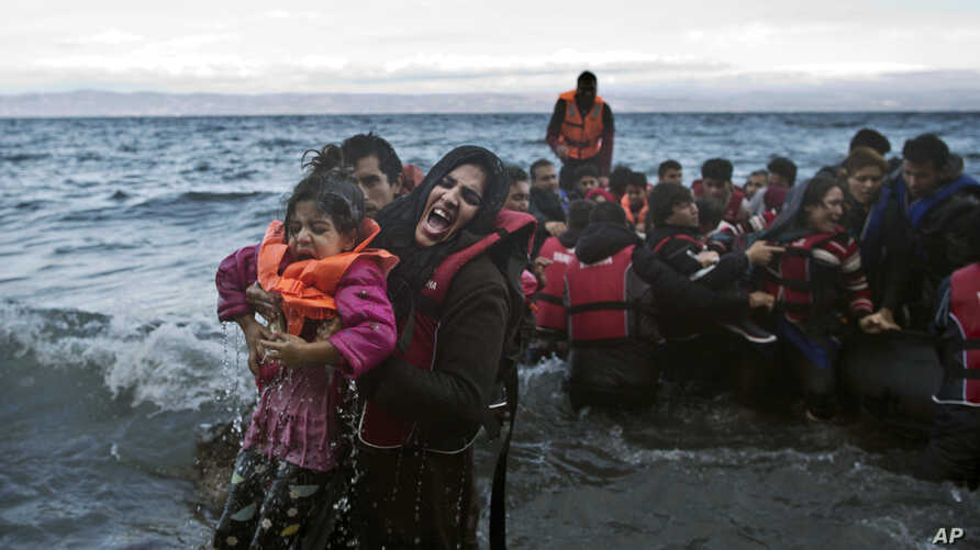 A woman screams for help after she and her daughter fell in the water as they arrive along the northeastern Greek island of Lesbos,  Oct. 2 , 2015.