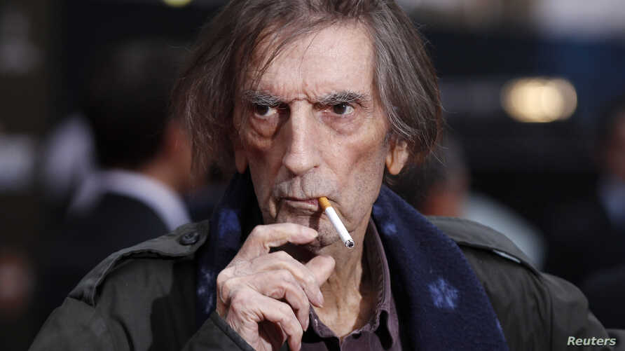 """FILE - Actor Harry Dean Stanton smokes a cigarette as he poses at the world premiere of the film """"Marvel's The Avengers"""" in Hollywood, California, April 11, 2012."""