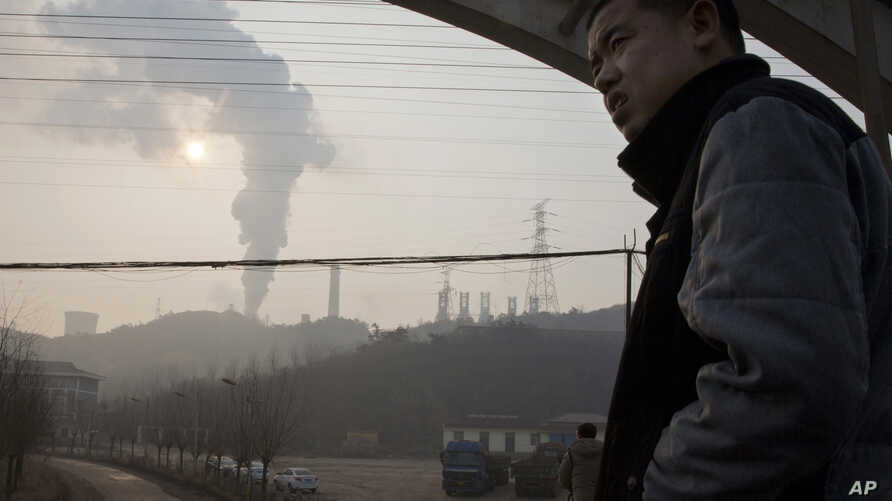 FILE - In this Dec. 30, 2016 photo, a man looks up near smoke spewing from a chimney near the Jiujiang steel and rolling mills in Qianan in northern China's Hebei province.