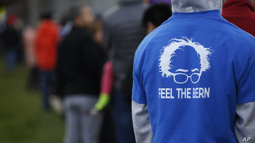 A man in a Bernie Sanders shirt waits in a line to vote at a Democratic caucus site Tuesday, March 22, 2016.