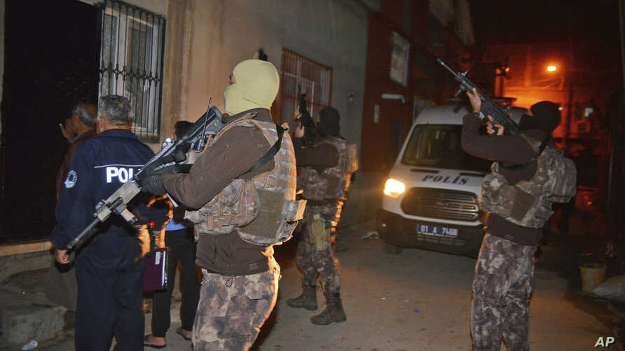 Masked Turkish police officers secure the perimeter outside a house during an operation to arrest people for alleged links to Islamic State group in Adana, Turkey, Nov. 10, 2017.