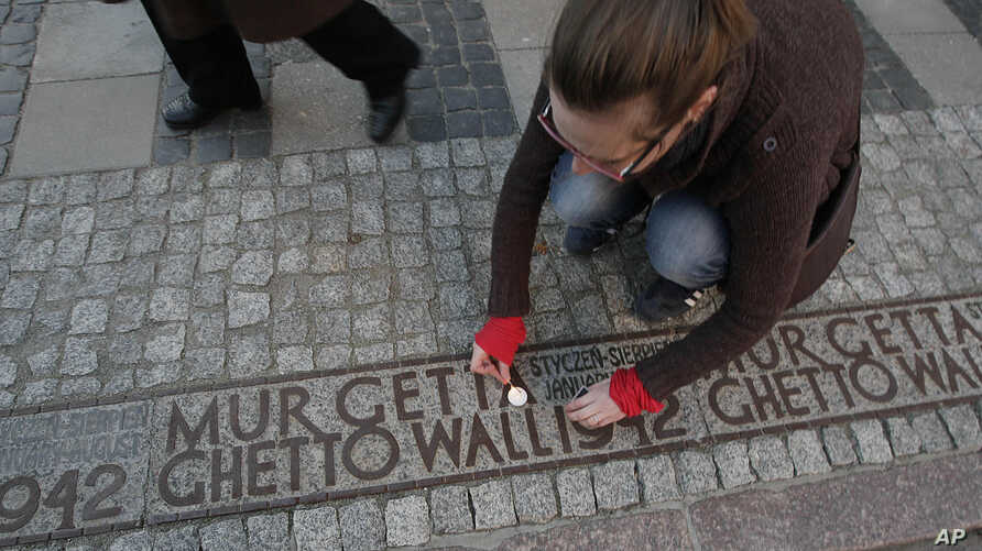 A woman lights a candle in a place where a border wall stood during World War II separating the Warsaw ghetto from the rest of the town, in Warsaw, Poland, April 21, 2013.