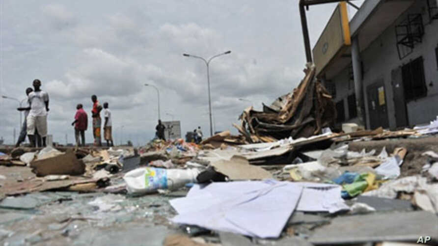 Resident walk past shops looted and destroyed in the Abobo district of Abidjan, March 2, 2011