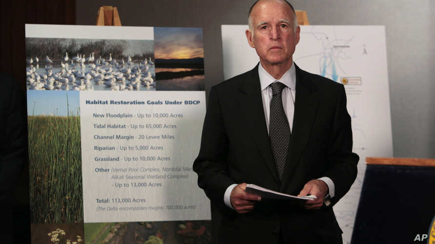FILE - California Gov. Jerry Brown waits for the start of a news conference to announce plans to build a giant twin tunnel system to move water from the Sacramento-San Joaquin River Delta to farmland and cities, in Sacramento, California, July 25, 20