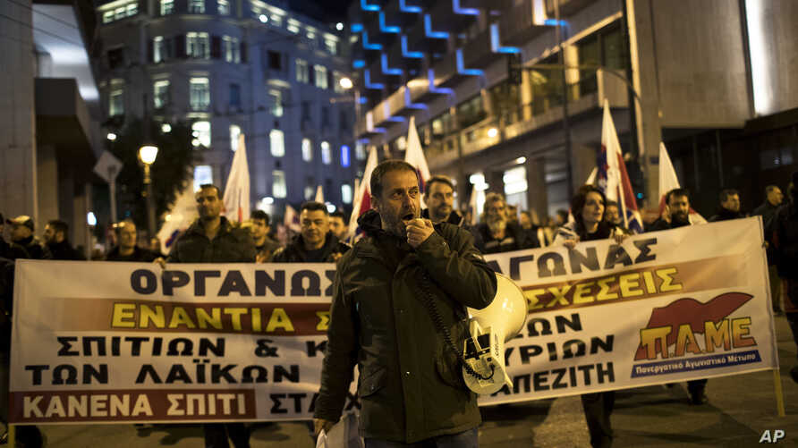 A protester shouts slogans during a demonstration against government plans to expand the number of auctions of foreclosed properties, in central Athens, Feb. 21, 2018.