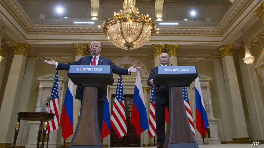 U.S. President Donald Trump, left, gestures while speaking as Russian President Vladimir Putin, right, listens during their joint news conference at the Presidential Palace in Helsinki, Finland, July 16, 2018.