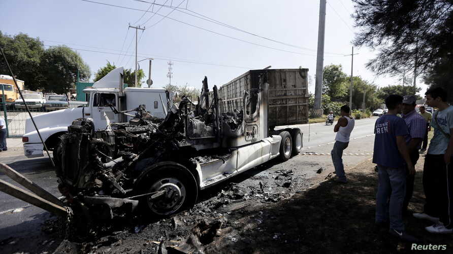 Men stand next to the wreckage of a tractor-trailer set ablaze by members of a drug cartel in Guadalajara, Mexico, May 1, 2015.