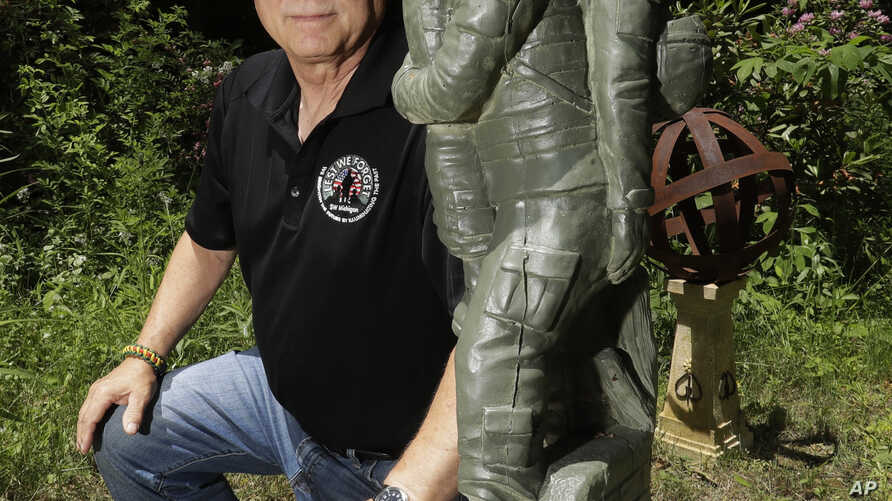 In a photo from June 9, 2017, former Army medic James McCloughan kneels next to a statue presented to him by a fellow soldier in South Haven, Michigan. McCloughan saved the lives of 10 soldiers during the Battle of Nui Yon Hill in May 1969 in Vietnam