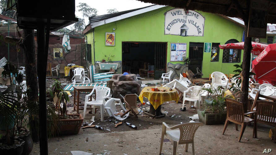 FILE - Damaged chairs and tables lie among the debris strewn after a bomb attack outside an Ethiopian restaurant in Kampala, Uganda, July 12, 2010.