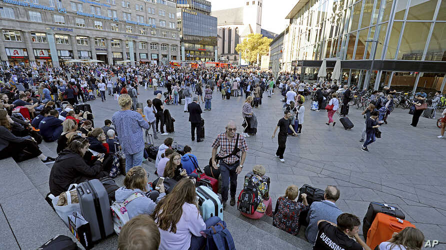 People wait outside the Cologne train station on Oct. 15, 2018. Cologne police closed parts of the western German city's main train station after a man took a woman hostage in a pharmacy inside.
