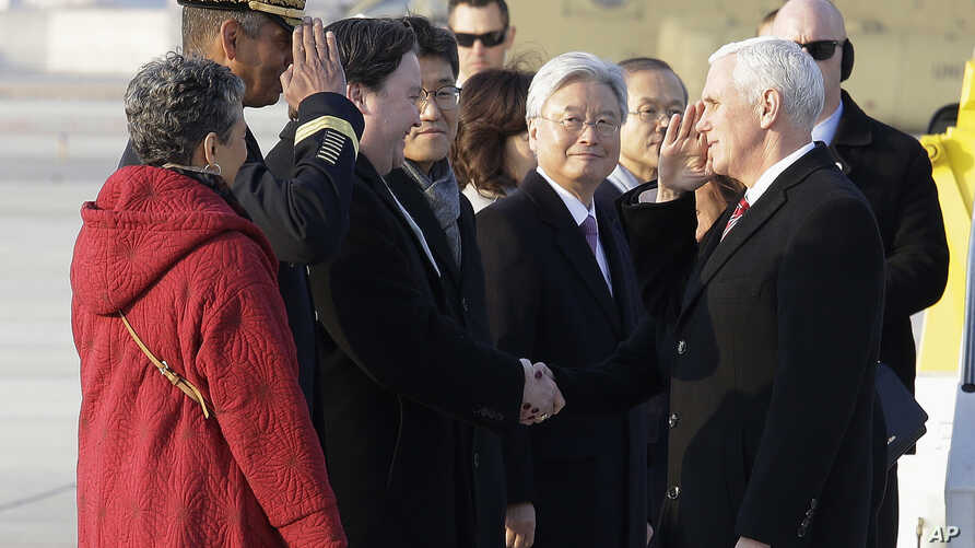 U.S. Vice President Mike Pence, right, and U.S. Gen. Vincent Brooks, commander of the United Nations Command, U.S. Forces Korea and Combined Forces Command, salute each other upon Pence's arrival at Osan Air Base in Pyeongtaek, South Korea, Feb. 8, 2