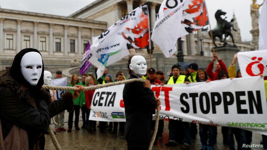 Demonstrators hold a rope during a protest against the Comprehensive Economic Trade Agreement (CETA) in front of the Parliament in Vienna, Austria Sept. 20, 2017.