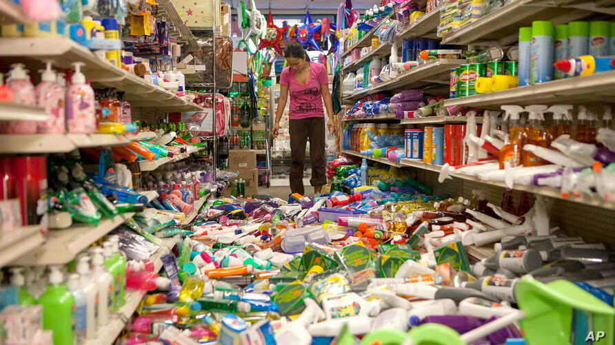 Nina Quidit cleans up the Dollar Plus and Party Supplies Store in American Canyon, California, after an earthquake, Aug. 24, 2014.
