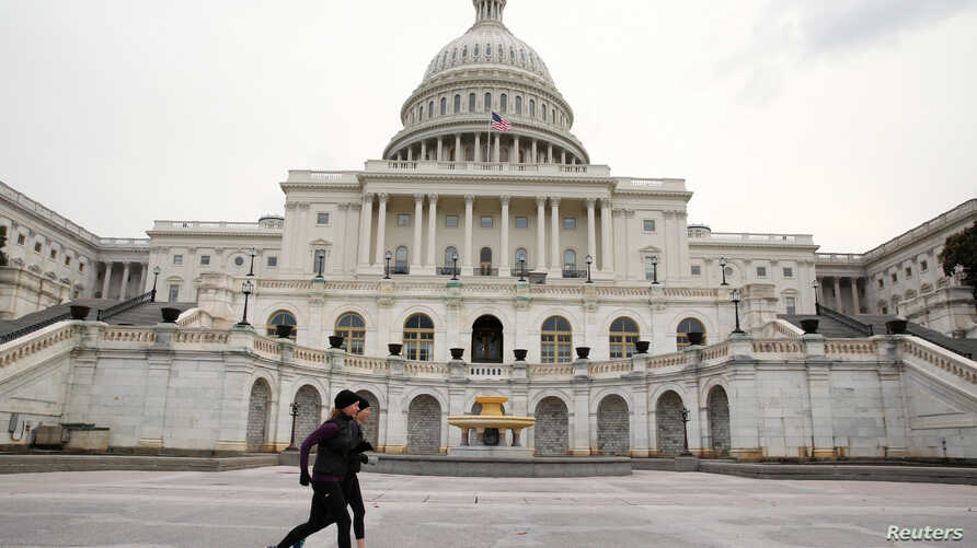 Runners stride past the U.S. Capitol building on the day of U.S. President Donald Trump's evening State of the Union address to a joint session of the U.S. Congress at the Capitol in Washington, U.S. Jan. 30, 2018.
