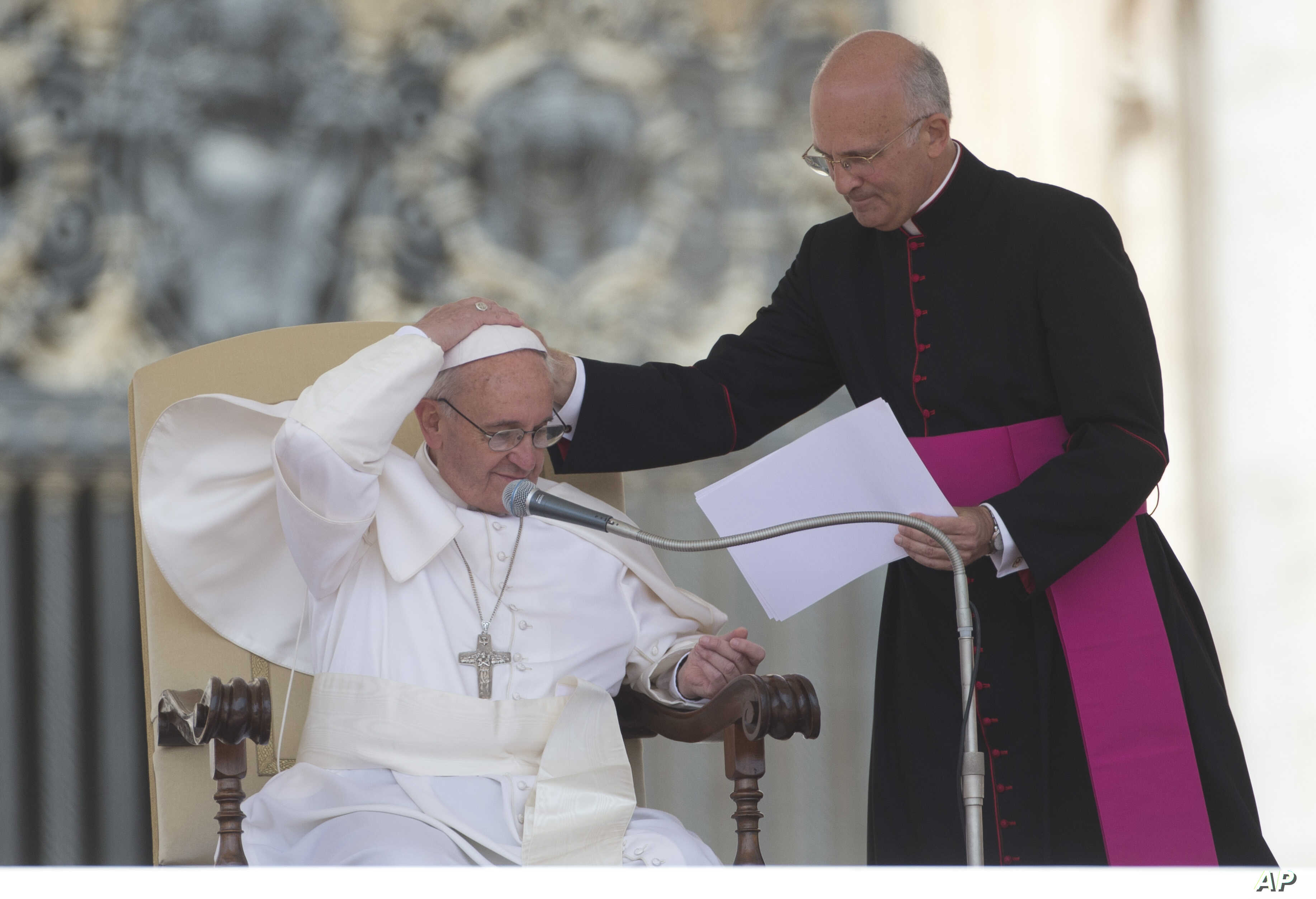 Pope Francis is helped by his personal secretary Mons. Alfred Xuereb, right, with his skull cap during a gust of wind while he attends his weekly open-air general audience in St. Peter's Square at the Vatican, Wednesday, May 22, 2013.