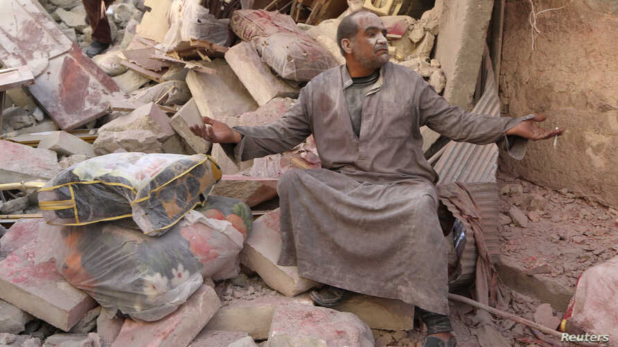 A survivor sits on the rubble of collapsed buildings at a site hit by what activists said was a barrel bomb dropped by forces loyal to Syria's President Bashar al-Assad in Aleppo's al-Sakhour district March 6, 2014. REUTERS/Hosam Katan