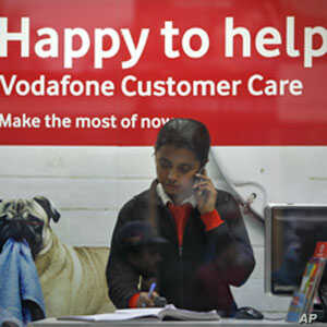 An employee talks on mobile phone inside a Vodafone store