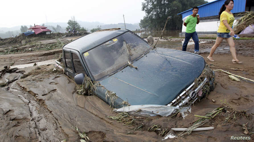 People walk past a car stranded in mud after heavy rainfalls hit Fushun, Liaoning province, August 17, 2013. Another 12 people were reported killed by floods in Liaoning province on Sunday, bringing the death toll in northeast China floods to 37, acc