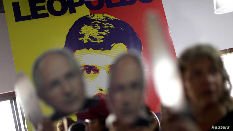 People hold portraits of opposition leader Antonio Ledezma in front of a wall with a portrait of opposition leader Leopoldo Lopez during a news conference at the Venezuelan coalition of opposition parties (MUD) headquarters in Caracas, Venezuela, Aug...