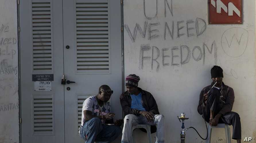 FILE - African migrants sit outside Holot detention center in the Negev Desert, southern Israel, April 21, 2015.