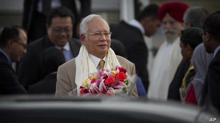 Malaysian Prime Minister Najib Razak holds a bouquet of flowers presented to him upon arrival in New Delhi, India, March 31, 2017.