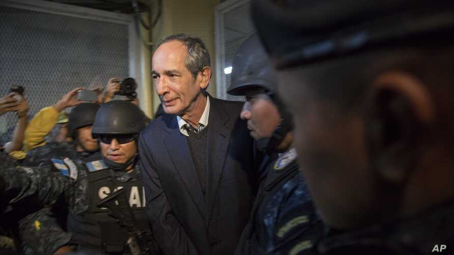 Former Guatemalan President Alvaro Colom is escorted by police to a courtroom in Guatemala City, Tuesday, Feb. 13, 2018.