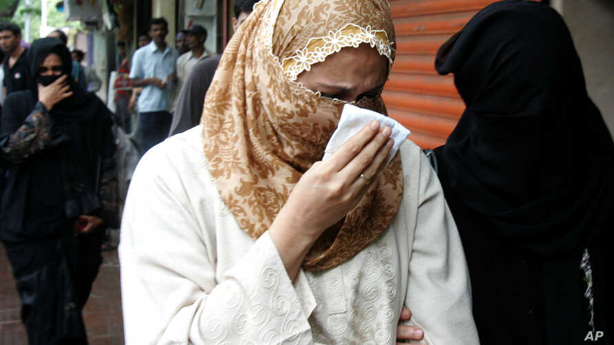 FILE - Raheen Memon, center, wife of Yakub Memon, reacts as she arrives at a special court trying cases of the 1993 Mumbai bombings that killed 257 people in Mumbai, India, July 27, 2007