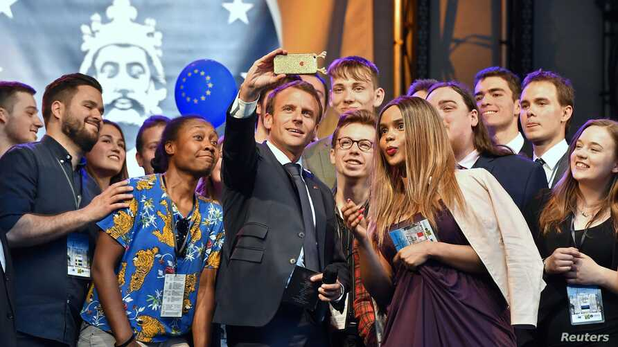 French president Emmanuel Macron takes a selfie with participants of the Charlemagne Youth Prize on the podium of a European Feast in Aachen, Germany, May 9, 2018.