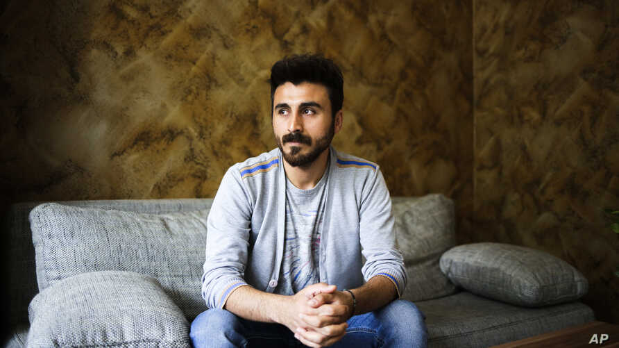 FILE - In this July 18, 2017 photo, Kurdish journalist Ismail Eskin poses for a photo during an interview with The Associated Press in Berlin. Eskin left Turkey just before he was sentenced to 3 1/2 years in prison on terrorism-related charges.