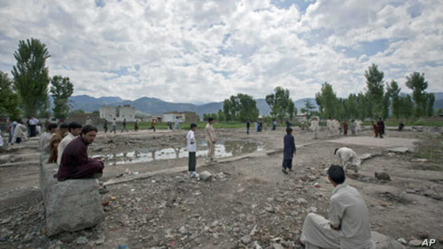 Residents sit near children playing cricket on the demolished site of a compound of Osama bin Laden, in Abbottabad, Pakistan, May 1, 2012.