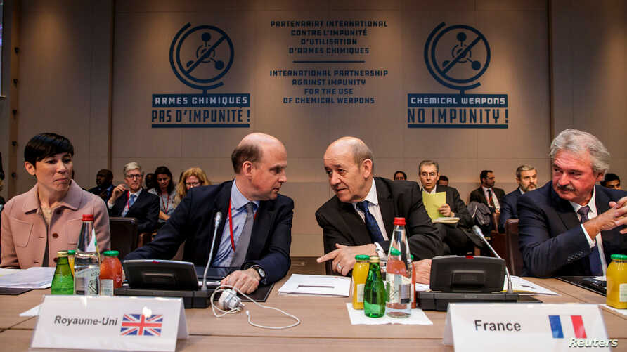 French Foreign Affairs Minister Jean-Yves Le Drian, 2nd from right, speaks with Angus Lapsley, Director for Defense at the British foreign affairs ministry, during a meeting on the International Partnership against Impunity for the Use of Chemical We