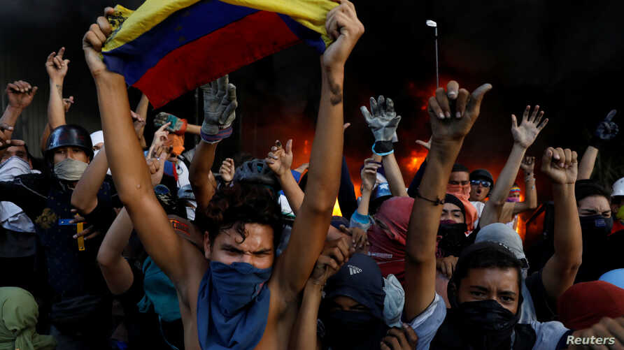 Protesters react in front of a fire burning at the entrance of a building, housing the magistracy of the Supreme Court of Justice and a bank branch, during a rally against Venezuela's President Nicolas Maduro, in Caracas, Venezuela, June 12, 2017.
