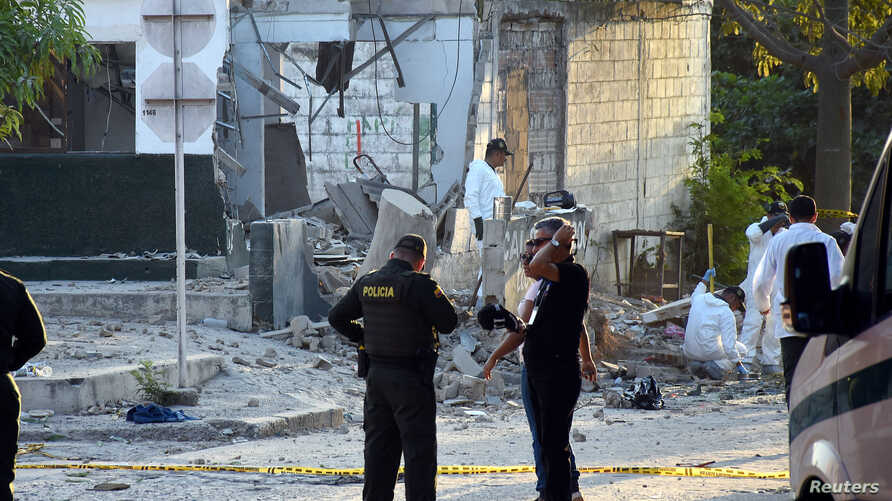 Police officers stand guard near the site of a bomb attack at a police station in Barranquilla, Colombia Jan. 28, 2018.