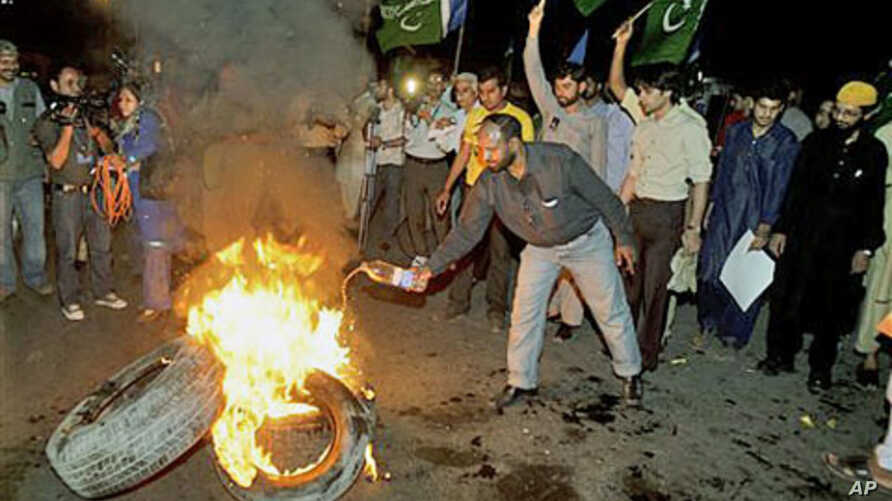 Pakistani protesters burn tires during a demonstration in Lahore, Pakistan, against the release of Raymond Allen Davis, an American CIA contractor, March 16, 2011
