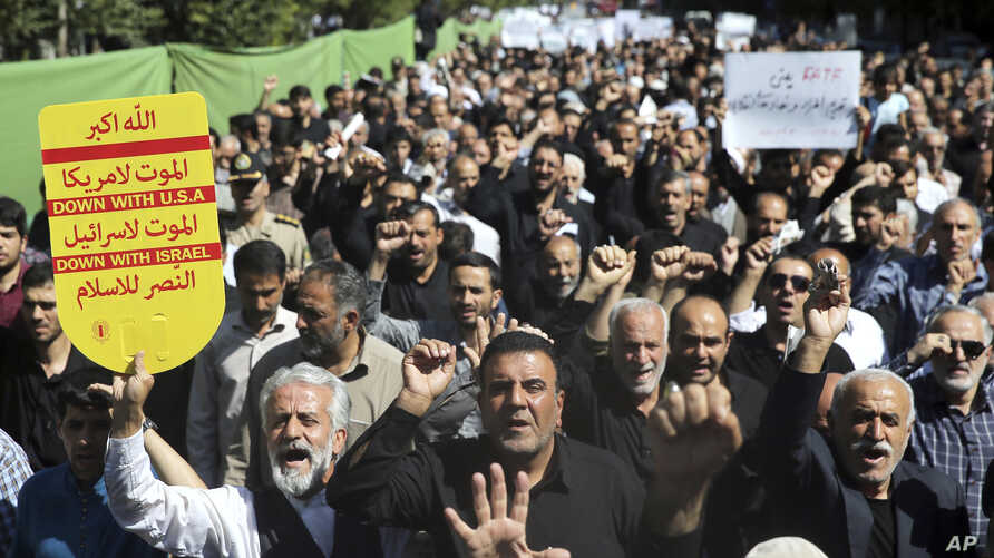 Worshippers chant slogans against America, Israel and Saudi Arabia, as one of them holds up an anti-American placard, in a rally to condemn the Sept. 22, 2018  terror attack in Ahvaz, after prayers in Tehran, Iran, Sept. 28, 2018.