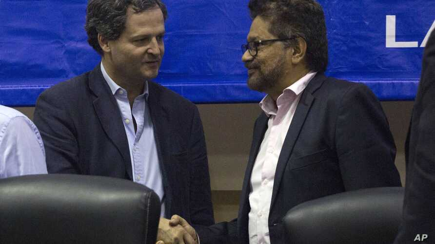 Ivan Marquez, chief negotiator of the Revolutionary Armed Forces of Colombia, right, and Sergio Jaramillo, Colombia's government peace commissioner, shake hands after a joint announcement on a request for a U.N. observer mission in Havana, Cuba, Jan.