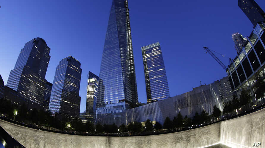 In this image made with a fisheye lens, One World Trade Center, center, rises above waterfalls at the National September 11 Memorial and Museum, Sept. 8, 2013, in New York.