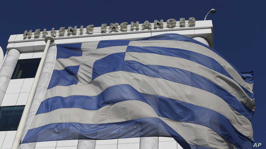 A Greek flag waves outside the Stock Exchange in Athens on Monday, Dec. 29, 2014.  Greece was forced Monday to call early national elections, stoking financial concerns as investors worry the main opposition party will win _ and want to renege on the