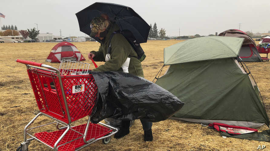 Amy Sheppard packs up items outside her tent in a Walmart parking lot in Chico, Calif., that's been a makeshift campground for people displaced by wildfire, Nov. 21, 2018. Sheppard lost her home in Magalia to the Camp fire.